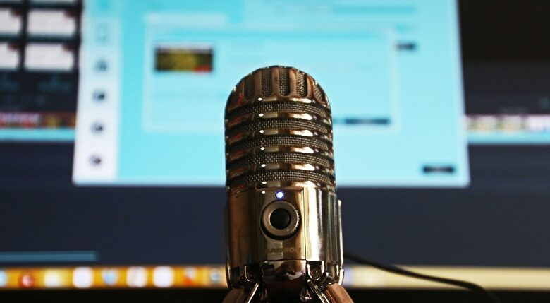 Microphone in front of a computer screen slightly blurred recording a podcast