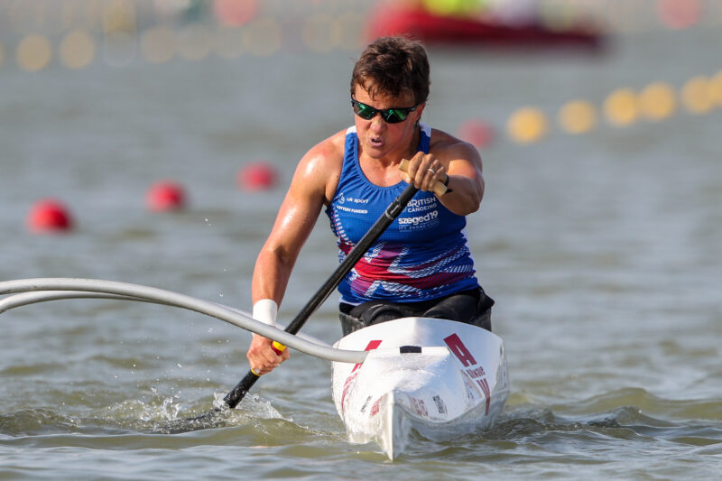Emma Wiggs sitting in canoe on water with paddle down wearing sunglasses. Emma is wearing a blue vest with image of british flag