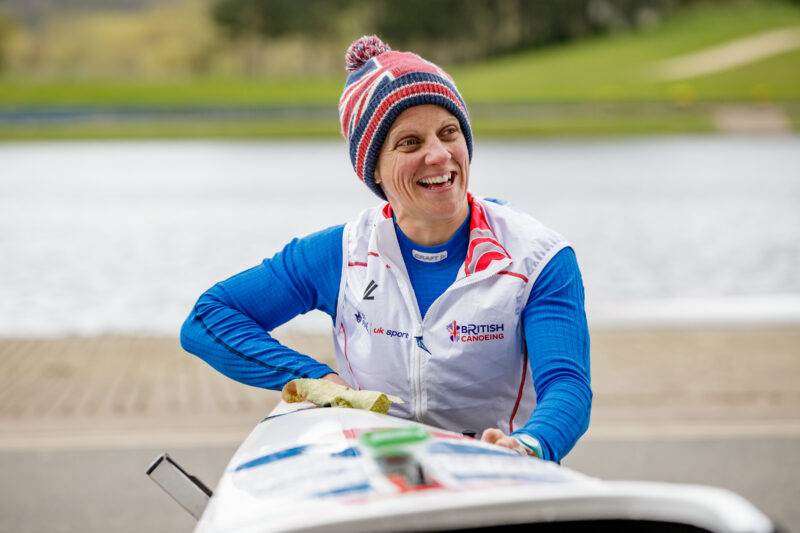 Emma Wiggs sitting in canoe smiling, wearing GB sports white jacket with hat design of British flag and pom pom at the back