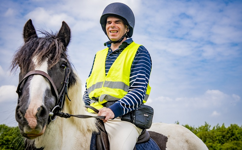 Simon wearing a blue and white striped T-shirt riding a black and white horse