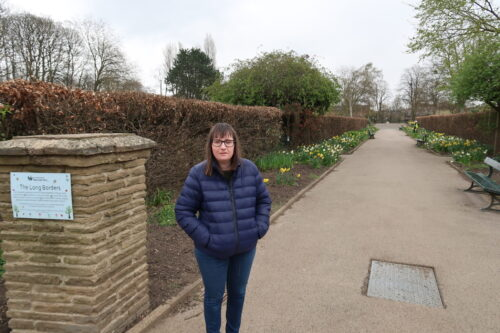 Holly-stood-on-a-stone-path-with-daffadils-and-brown-hedges-at-either-side-she-is-wearing-a-blue-padded-jacket-blue-jeans-and-grey-trainers-