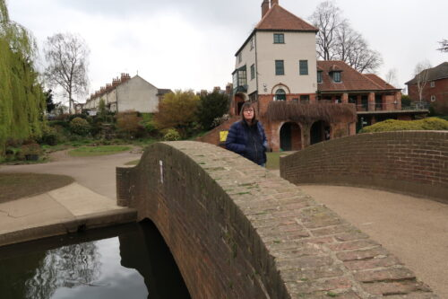 Holly-stood-on-a-stone-bridge-with-her-hands-in-her-pockets-she-is-wearing-a-blue-padded-jacket-and-blue-jeans-there-is-a-stone-building-in-the-background-2048x1365