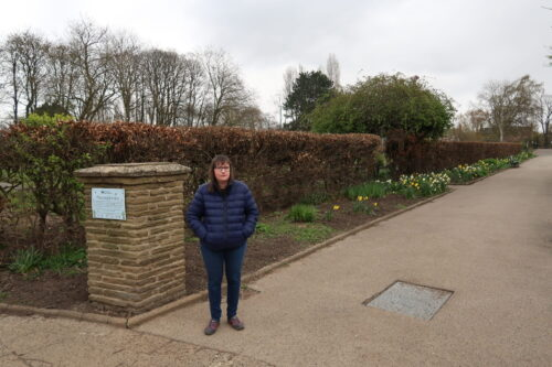 Holly-stood-on-a-stone-path-with-daffodils-and-brown-hedges-to-the-side-of-her-she-is-wearing-a-blue-padded-jacket-blue-jeans-and-grey-trainers-