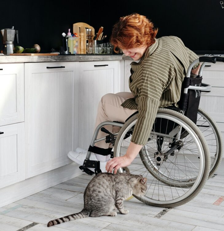 Woman in a wheelchair in her white kitchen stroking her cat on the floor