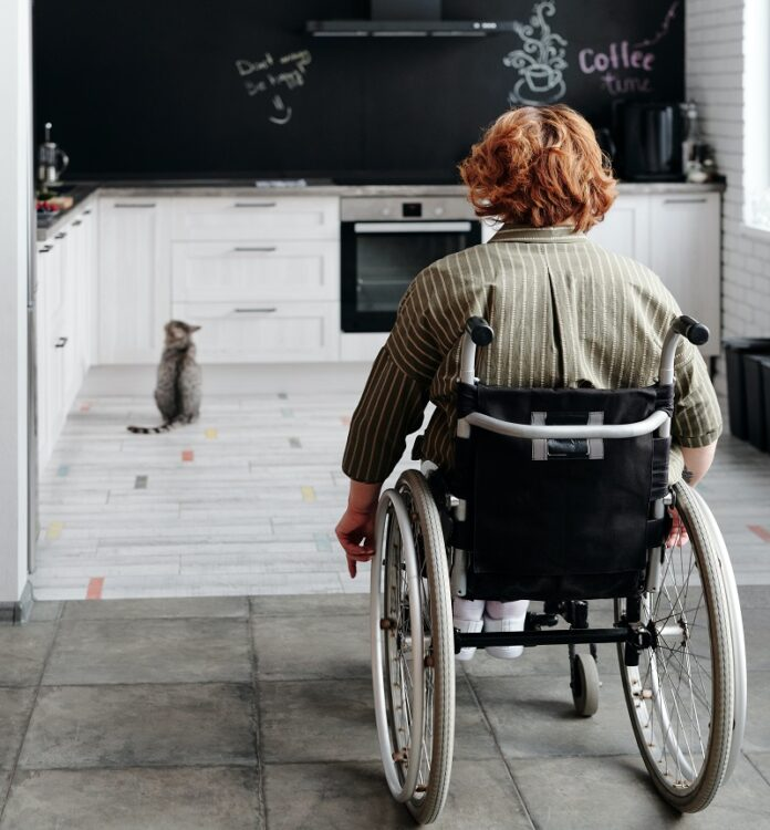 Woman in her wheelchair wheeling into her white kitchen from her open-plan dining room
