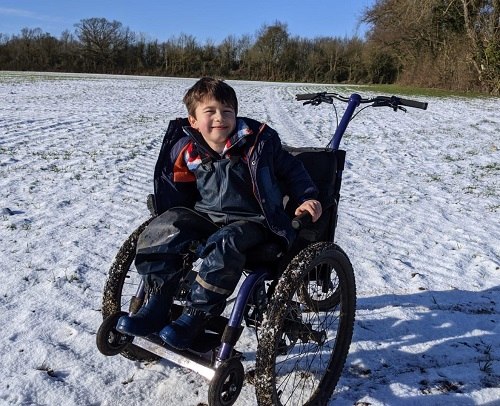 Archie in his Mountain Trike all-terrain wheelchair in a snow-covered field