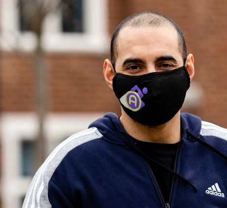Close up of Paralympian Ali Jawad wearing a blue hoodie and face mask