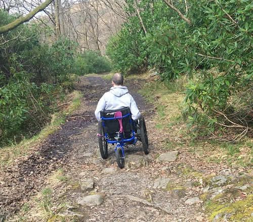 Gary in a woodland on rough ground in his Mountain Trike all-terrain wheelchair