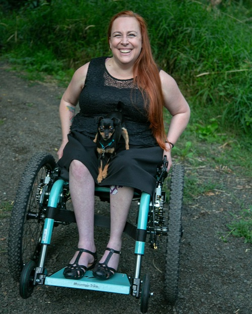 Nalani in her Mountain Trike all-terrain wheelchair in a wood with her dog on her lap