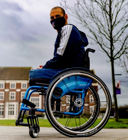 Paralympian Ali Jawad in his wheelchair outside wearing jeans, a blue hoodie and face mask