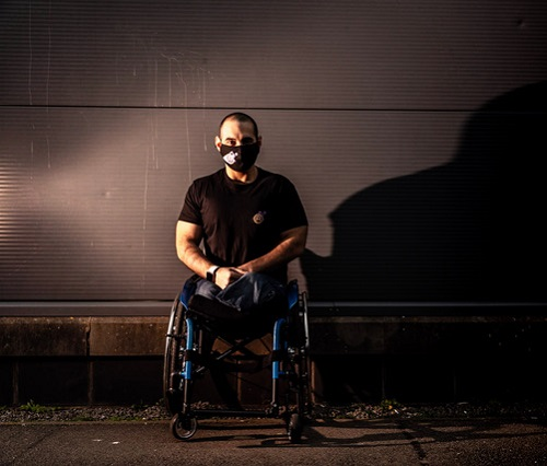 Paralympian Ali Jawad in his wheelchair wearing jeans, a black t-shirt and face mask against a brick wall in darkness