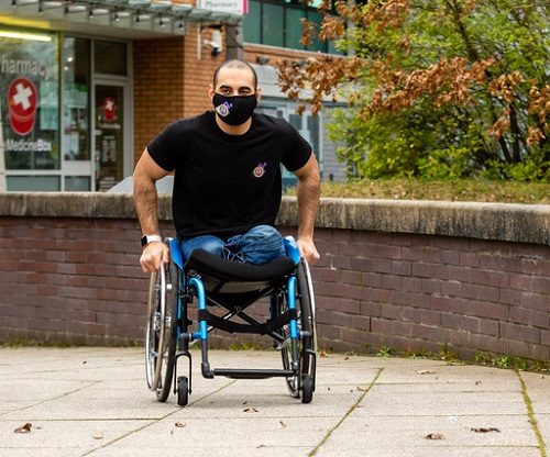 Paralympian Ali Jawad pushing his wheelchair wearing jeans, a black t-shirt and face mask
