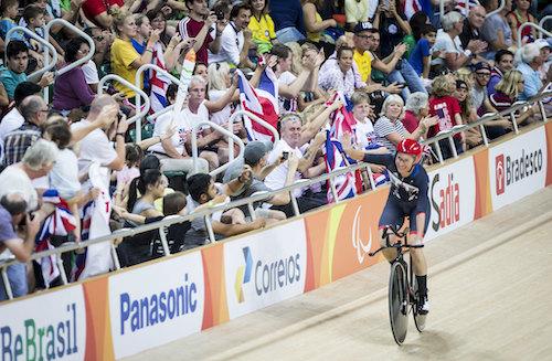 Sarah Storey riding her bike waving at the crowd