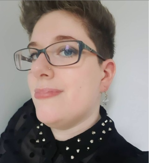 Close up head shot of disabled blogger Dax with short spiky hair, black glasses and a black lace top