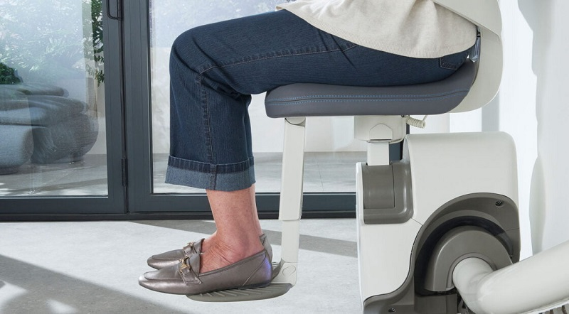 Flow X stairlift footrest viewed from the side with an older woman