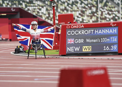 Hannah Cockroft holding union jack flag in her racing chair next to the digital board which shows T34 100 WR 16.39