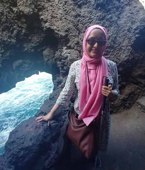 Nanjiba wearing glasses, a pink hijab, a denim jacket and dress standing next to water at a cove