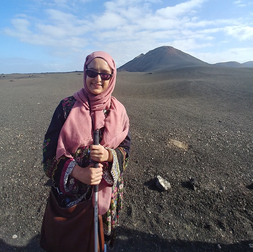 Nanjiba wearing glasses, a pink hijab and dress standing with her white cane in a dessert with a sand dune behind her