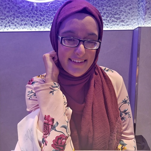 Nanjiba wearing glasses, a pink hijab and white top with pink flowers, sat in a restaurant