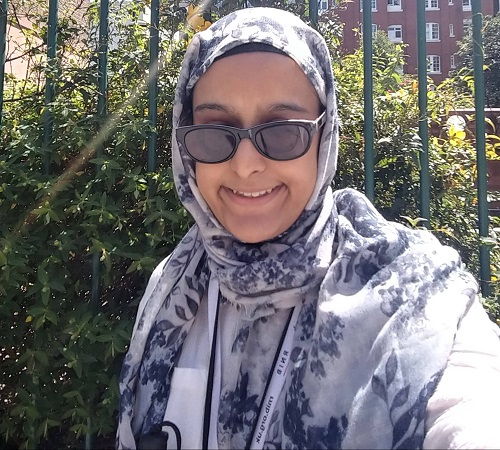 Nanjiba wearing glasses and a white hijab with blue flowers in a park in front of greenery