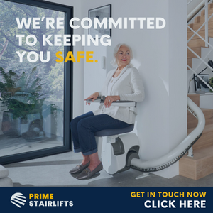 """Image is a photograph of an older lady in a stylish, modern home, seated on a stairlift at the bottom of a curved staircase. Text on the image reads: """"We're committed to keeping you safe. Prime Stairlifts. Get in touch now click here""""."""