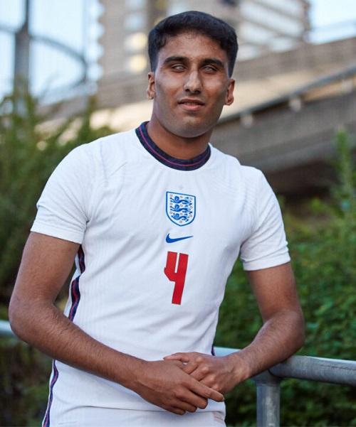 Blind footballer Azeem wearing an England football shirt