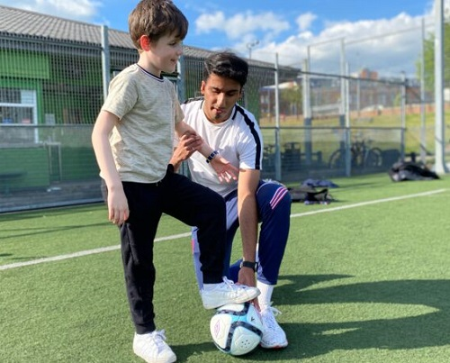 Visually impaired footballer Azeem showing a young boy to play football